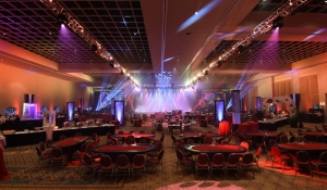 Blue Spark - Casino Royale theme party, casino tables, red, black, metal bead towers, columns, lighting, three screens, large dice, 007, cards