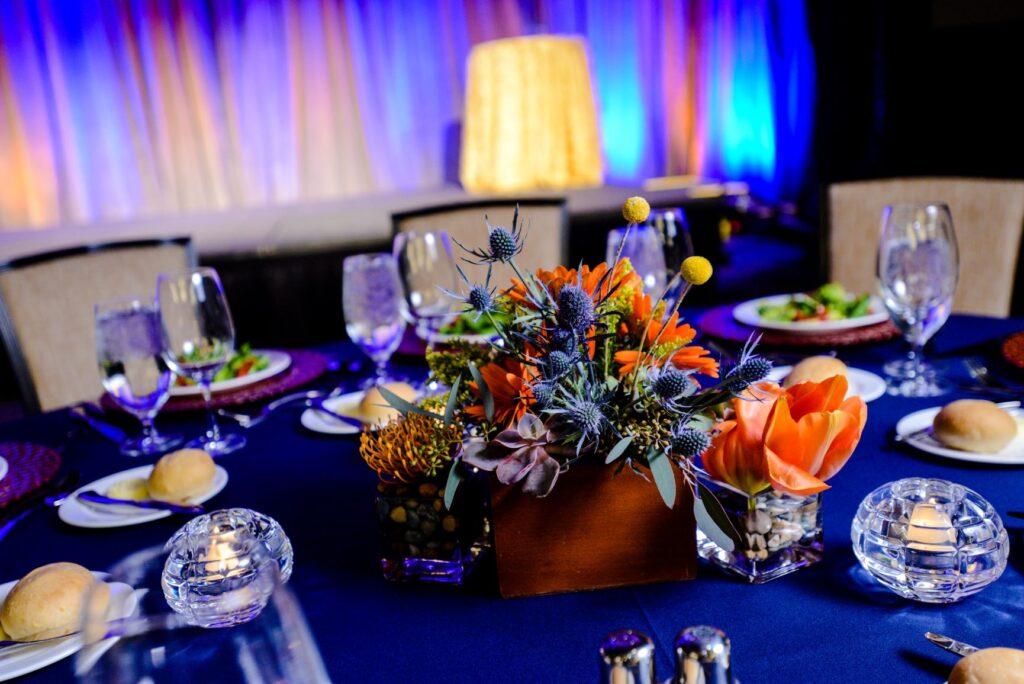 Custom event design blue table and brght orange centerpiece