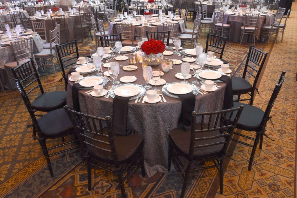 Custom event design silver and black table with red rose centerpiece
